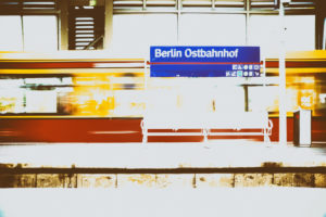 A platform of the Berlin Ostbahnhof with a grid bench and an incoming streetcar in Berlin.