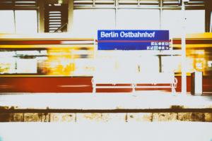 Ein Bahnsteig des Berliner Ostbahnhofes mit einer Gitterbank sowie einer einfahrenden Straßenbahn in Berlin.