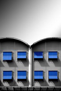 Moderne Wellblechfassade eines Wohnhauses mit Fensterreihen und blauen Markisen,