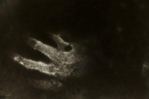 Handabdruck in einer dünnen Schneedecke, verfremdet