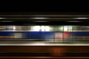 Bahnsteig des Bahnhofes Weinheim in der Nacht Sitzplätzen an einer Glastrennwand und einem vorbeifahrenden Zug