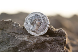 Finding of a Roman denarius by an archaeologist