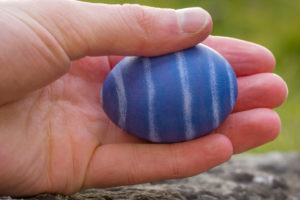 Hand holding blue and white striped Easter egg