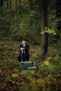Mann sitzt im Wald mit Hut und Stock und zwei Koffer