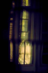 altes Fenster in einem Herrenhaus mit Fensterladen geschlossen im Gegenlicht und Sonne unscharf