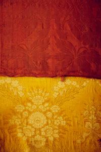alter Stoff aus Samt in den Farben gelb rot und Muster mit Blumen abgenutzt