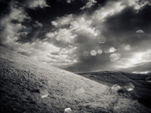Berg mit Wiese Wolken und Sonne, schwarz-weiß