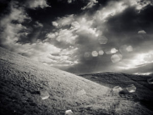mountain with meadow, clouds and sun, black and white