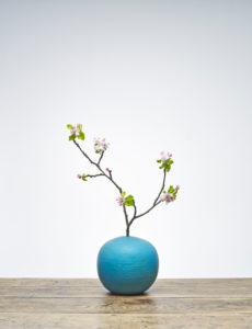 Blaue Vase mit Apfelzweig und Blüten auf Holztisch