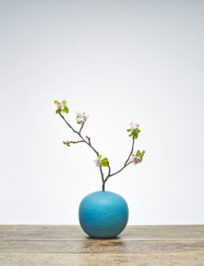 Blue Vase with apple branch and flowers on wooden table