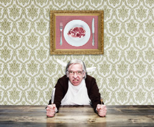 man wiht grey hair and glasses on the table, is holding knife and fork, photo with meat on the wall