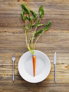 Karotte auf Teller, Besteck, Messer und Gabel auf altem Holztisch, von oben