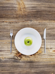 green apple on white plate, cutlery, knife and fork on old wooden table, from above
