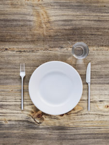 Empty plate, cutlery and glass on old wooden table, from above
