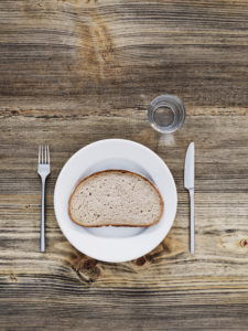 one slice of bread on plate, cutlery and glass on old wooden table, from above