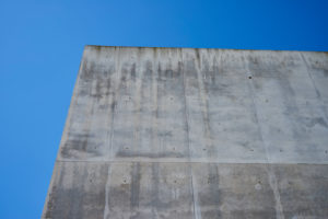 Concrete grey wall with structure and inclusions as a background in front of sky blue cloudless