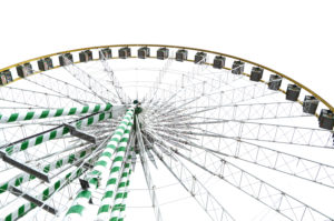 Ferris wheel with gondola in worm's eye view in front of white sky, cut out