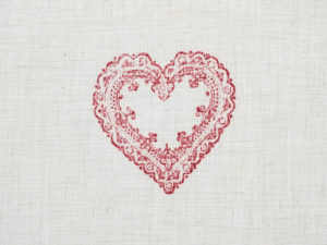 Heart with embroidery on a piece of linen fabric as a rectangle