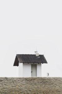 kleines Haus auf einem Deich im Winter, Himmel grau weiß, Raureif
