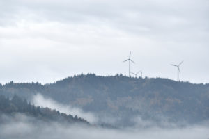 three wind turbines on a mountain in the Black Forest, forest, rain and fog