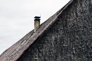 Dach mit Ziegeln und Kamin, alte Schindeln, grau und verwittert an einem Holzhaus im Schwarzwald