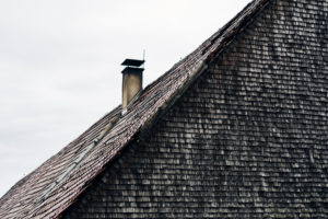Roof with bricks and fireplace, old shingles, grey and weathered on a wooden house in the Black Forest