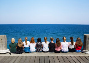 A group of girls sit next to each other on the pier and look at the sea, Heligoland, Schleswig-Holstein, Germany