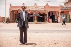 Old man gesturing at the camera, wrinkled face, broadcasting, Morocco, Ouarzazate