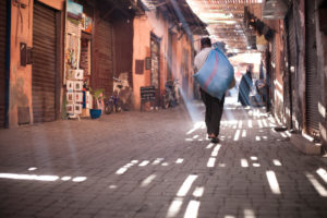Medina market, man is carrying a sack, market, Medina, play of lights, ornaments, shadow, light beams, Marrakech, Morocco,