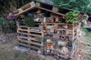 Large insect hotel made of pallets, perforated stones and many natural materials