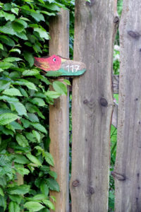 House number plate with bird motif on the wooden fence