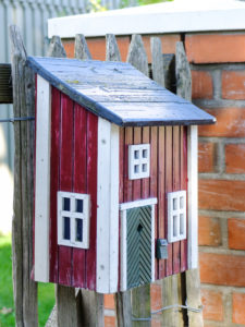 Mailbox on the wooden fence in the style of a typical Swedish house