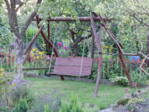 Self-made porch swing made of massive tree trunks in the garden