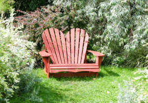 Red heart shaped Adirondack Chair in the garden
