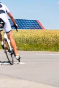 Road cyclist on country road, solar systems in the cornfield under a blue sky