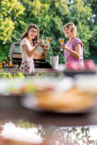 Young woman and mother have fun, laugh, barbecue, toasting