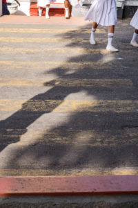 Legs of school children in uniform cross the street, crosswalk