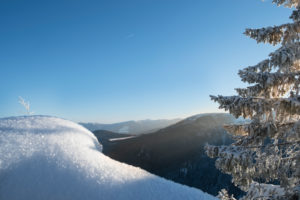 Snow-covered tree and rocks in wintry landscape with a view of the valley in front of sunny, blue sky in the Vosges Mountains, France