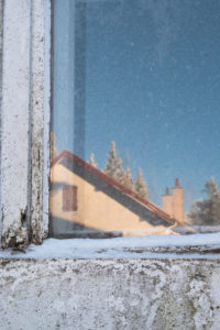 Snow-covered, old windowpane with reflection of a sunny, wintry landscape and hut in the Vosges, France