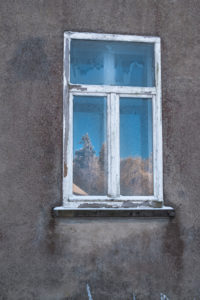Old windowpane with frosted flowers and reflection of a sunny, wintry landscape in gray facade in Vosges, France