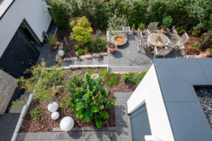 Overview of a neat garden landscape with a terrace, plant beds and access paths