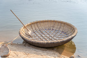 Raffia coracle moored to stone