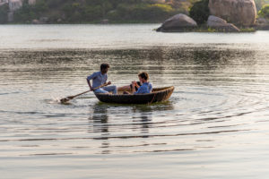 Coracle rows with passengers over reservoir