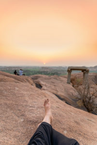 Legs of the photographer relaxing in the evening on a rock