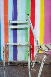 two old metal chairs with peeling paint against a colorful striped wall
