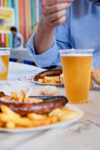 A man in a blue shirt is sitting in front of a plate of bratwurst and fries, and beer from plastic cups