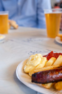 Plate with sausage and chips red and white, with beer from plastic cups