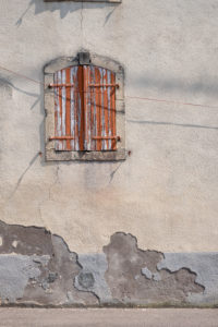Windows in a weathered plaster facade with brown wooden shutters and peeling paint