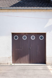 brown wooden garage door with four round windows in a residential building with white plaster facade