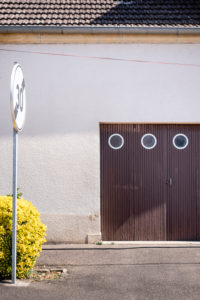 brown wooden garage door with three round windows in a residential building with white plaster facade at the end of a Tempo 30 zone